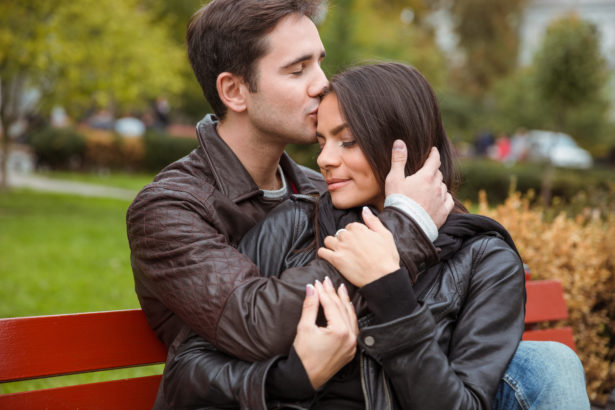 Couple hugging outdoors on the bench